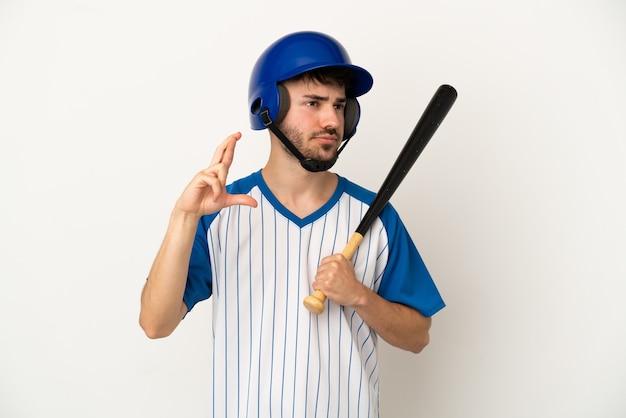 Молодой кавказский человек играет в бейсбол на белом фоне со скрещенными пальцами и желает лучшего