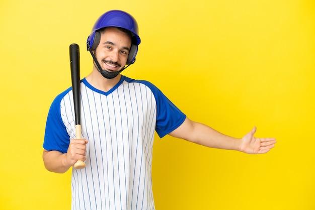 Молодой кавказский мужчина играет в бейсбол на желтом фоне, протягивая руки в сторону, приглашая приехать