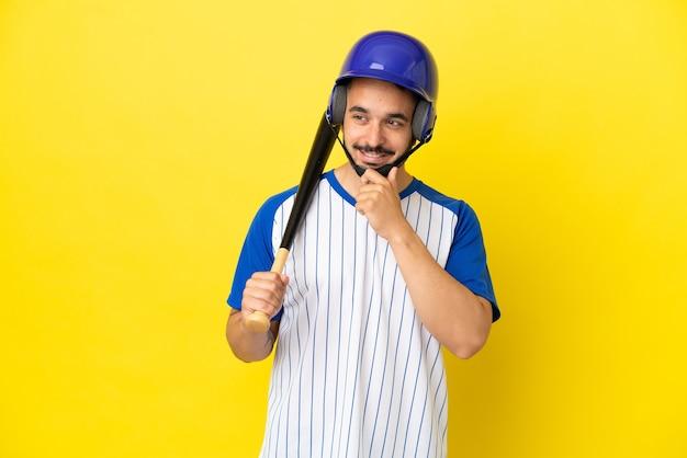 横を見て笑って黄色の背景に分離された野球をしている若い白人男性