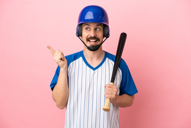 Young caucasian man playing baseball isolated on pink background intending to realizes the solution while lifting a finger up