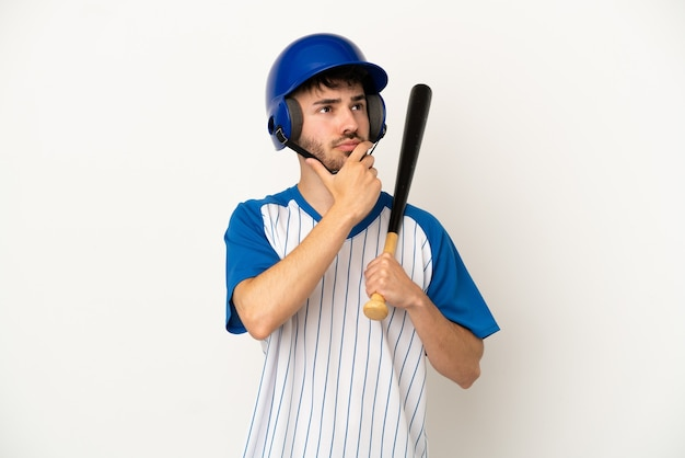 Young caucasian man playing baseball isolated on white background having doubts
