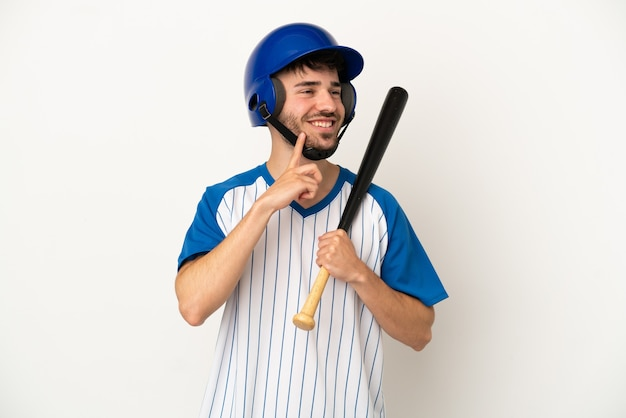 Young caucasian man playing baseball isolated on white background thinking an idea while looking up