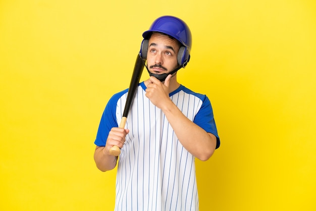 Young caucasian man playing baseball isolated on yellow background having doubts