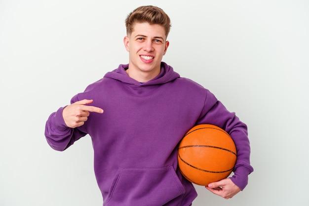 バスケットボールをしている若い白人男性は、シャツのコピースペースを手で指している孤立した背景の人、誇りと自信を持って