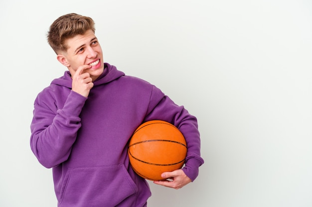 バスケットボールの孤立した背景を遊んでいる若い白人男性は、コピースペースを見ている何かについて考えてリラックスしました。