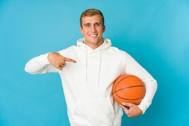 神経質で非常に不安な、青い背景の爪を噛んで孤立したバスケットボールをしている若い白人男性。