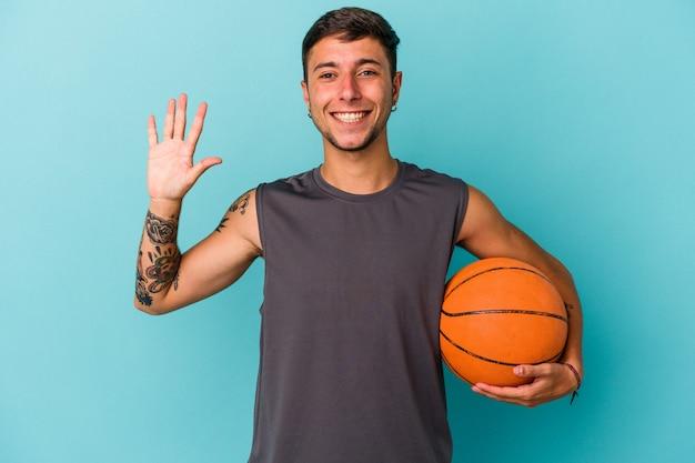 青い背景に分離されたバスケットボールをしている若い白人男性は、指で5番を示して陽気に笑っています。