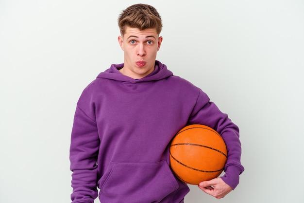 バスケットボールの孤立した壁を遊んでいる若い白人男性は、肩をすくめ、目を開けて混乱しました。