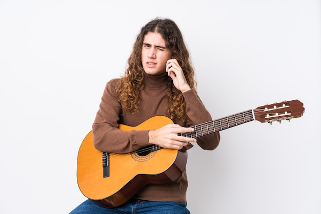 Young caucasian man playing guitar isolated covering ears with hands.