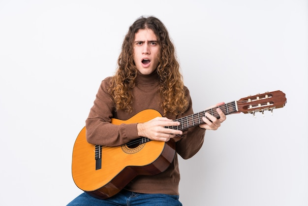 Young caucasian man playing guitar isolated screaming very angry and aggressive.