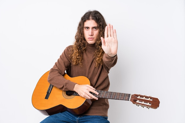 Young caucasian man playing guitar isolated standing with outstretched hand showing stop sign, preventing you.