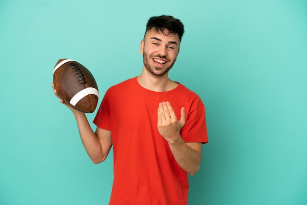 Young caucasian man playing rugby isolated on blue background inviting to come with hand. happy that you came
