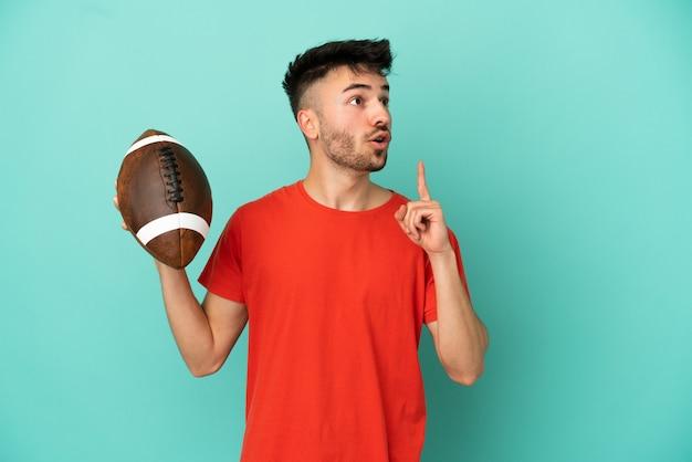 Молодой кавказский человек играет в регби на синем фоне, думая об идее, указывая пальцем вверх