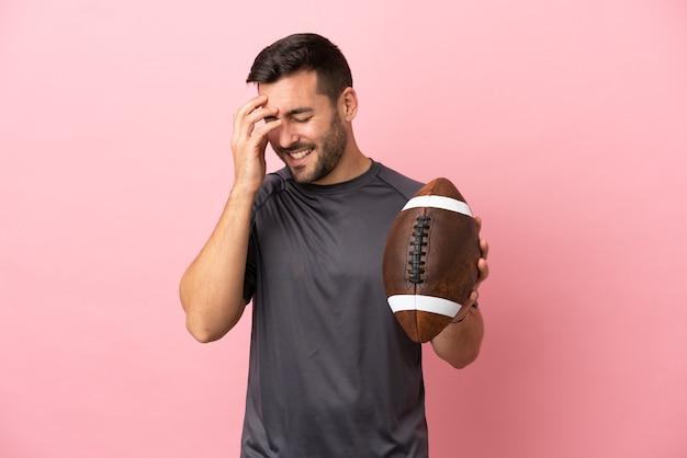 Молодой кавказский человек играет в регби на розовом фоне смеясь
