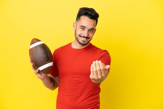 手で来るように誘う黄色の背景に分離されたラグビーをしている若い白人男性。あなたが来て幸せ