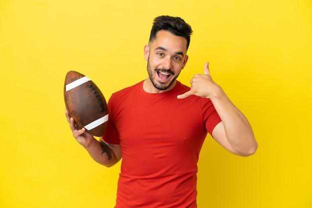 Молодой кавказский человек играет в регби на желтом фоне, делая телефонный жест. перезвони мне знак
