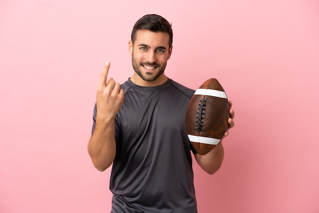 Young caucasian man playing rugby isolated on pink background doing coming gesture