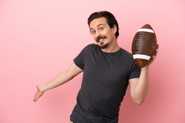 Young caucasian man playing rugby isolated on pink background extending hands to the side for inviting to come
