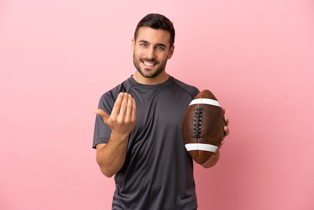 Young caucasian man playing rugby isolated on pink background inviting to come with hand. happy that you came