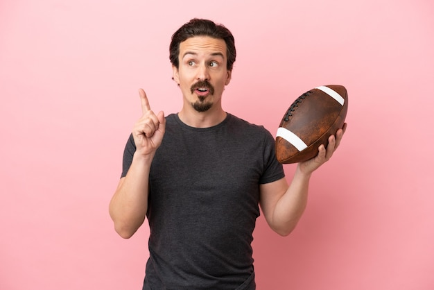 Young caucasian man playing rugby isolated on pink background thinking an idea pointing the finger up