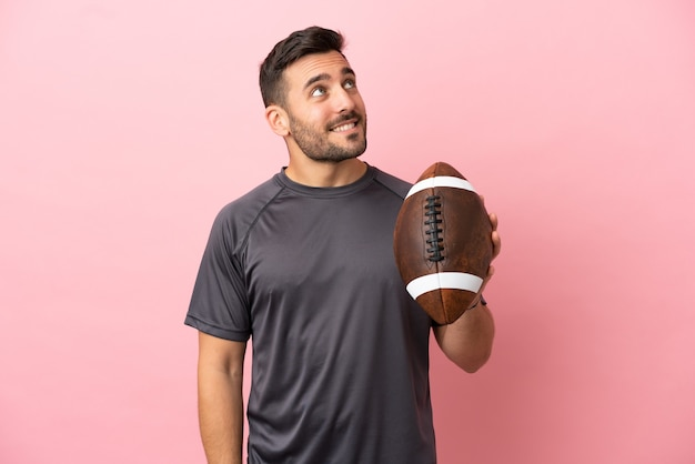 Young caucasian man playing rugby isolated on pink background thinking an idea while looking up