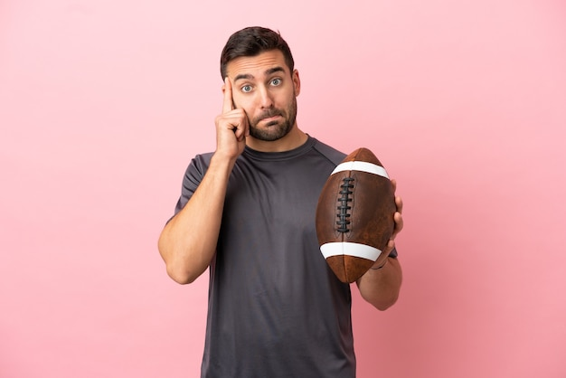 Young caucasian man playing rugby isolated on pink background thinking an idea