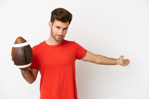 Young caucasian man playing rugby isolated on white background extending hands to the side for inviting to come