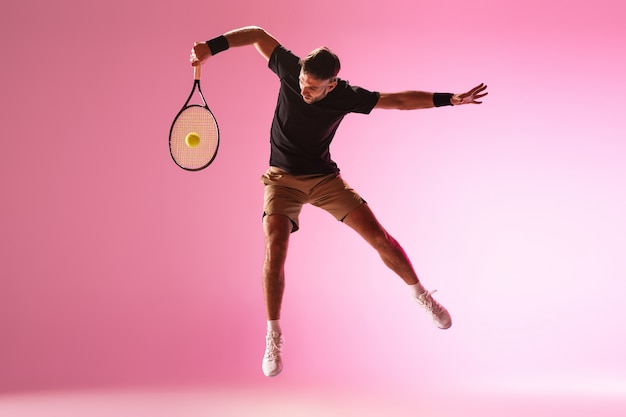 Young caucasian man playing tennis isolated on pink  wall action and motion concept