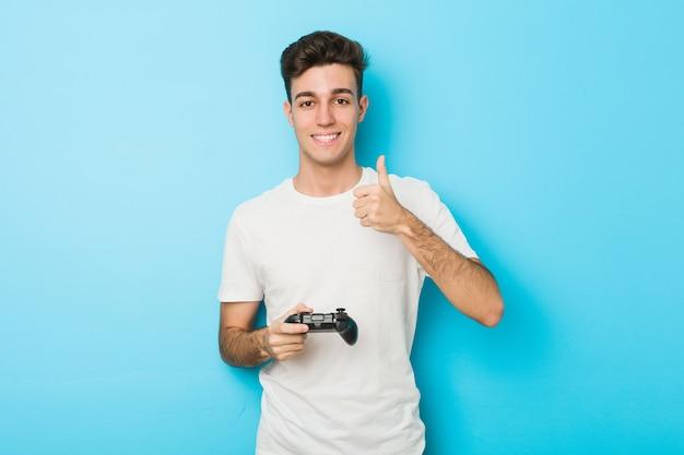 Молодой кавказский человек играет в видеоигры с игровым контроллером, улыбаясь и поднимая палец вверх