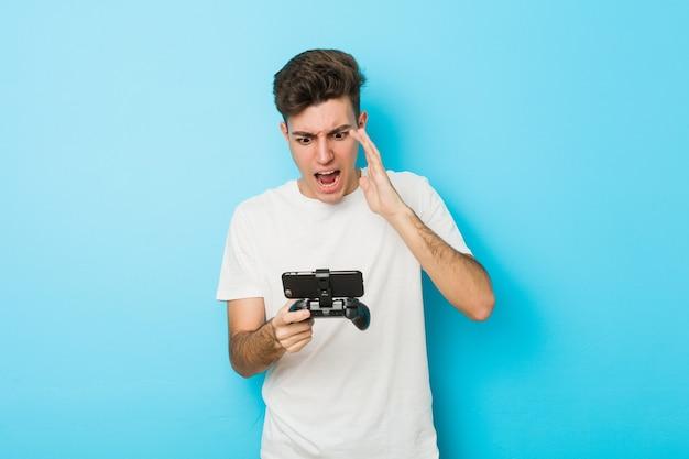 Молодой кавказский человек играет в видеоигры с телефонным криком, возбужденным вперед.