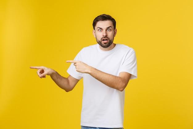 노란색에 흥미로운 뭔가 가리키는 젊은 백인 남자.