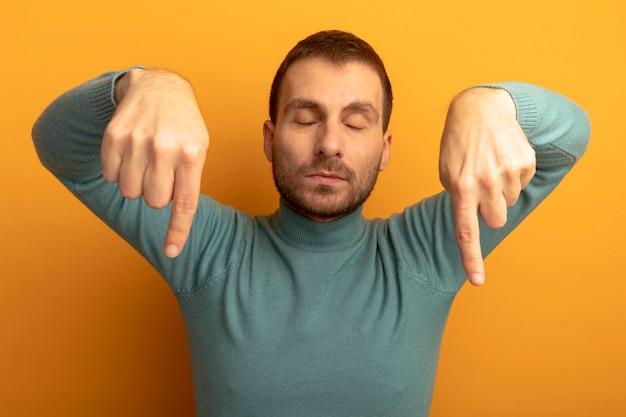 オレンジ色の壁に隔離された目を閉じて下向きの若い白人男性