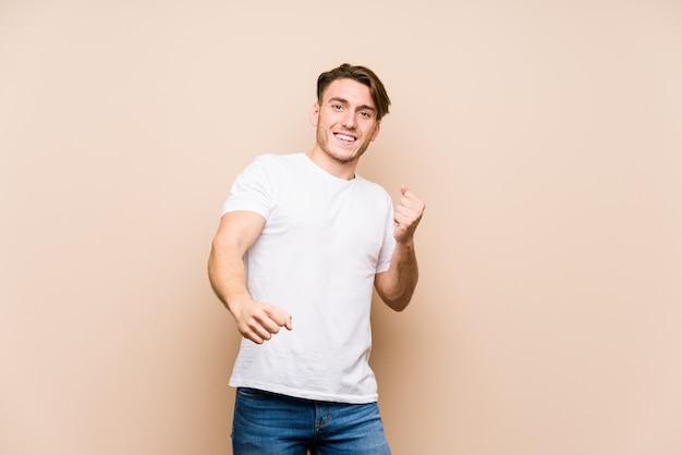 Young caucasian man posing dancing and having fun.