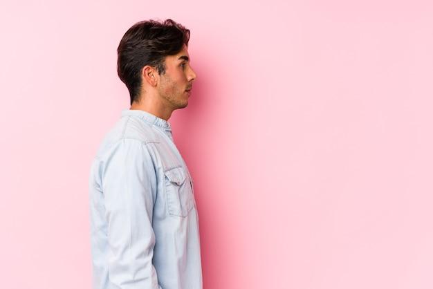 Молодой кавказский человек позирует в розовом изолированном, глядя влево, боком.
