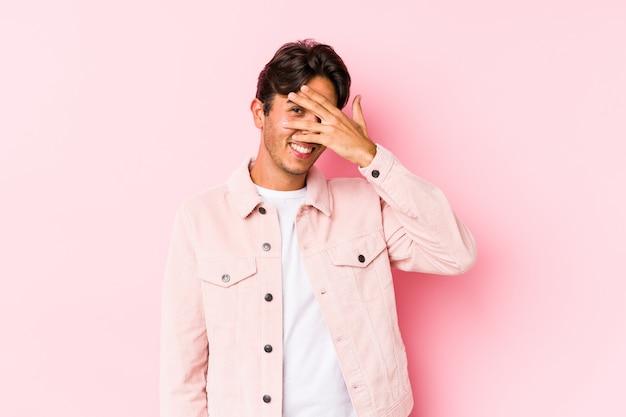 Молодой кавказский человек представляя в розовой стене моргает на камере через пальцы, смущенный покрывать лицо.