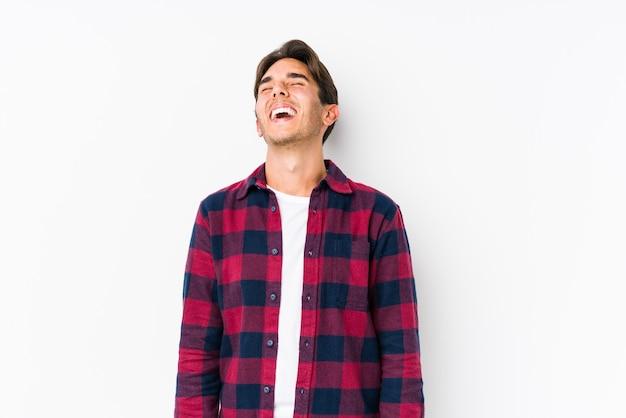 Молодой кавказский мужчина позирует в розовой стене изолировал расслабленный и счастливый смех, вытянув шею, показывая зубы.