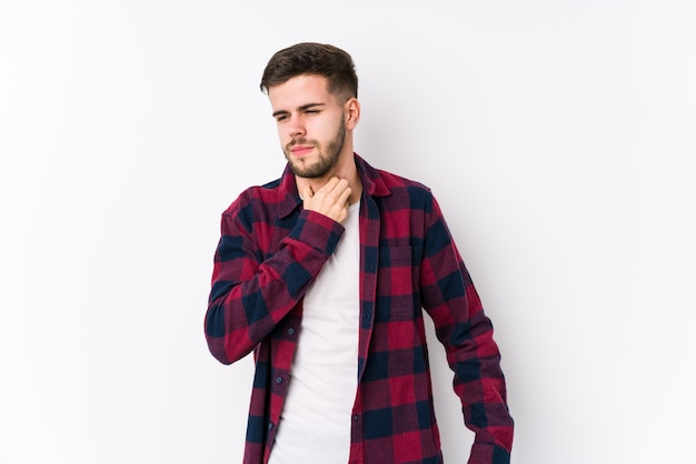 孤立した白でポーズをとる若い白人男性は、ウイルスや感染症のために喉の痛みに苦しんでいます。