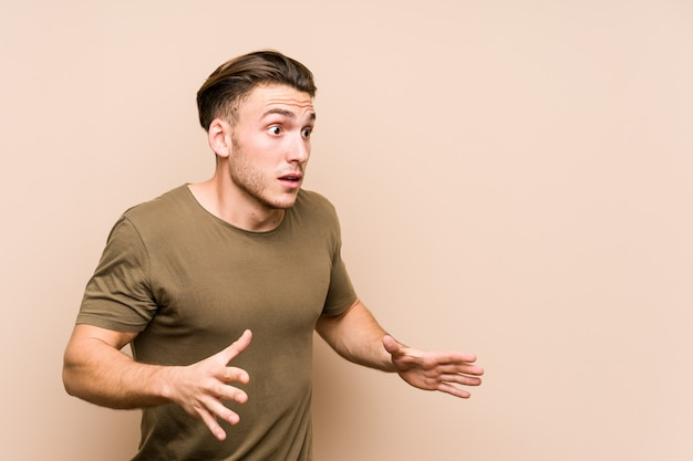 Young caucasian man posing isolated shouts loud, keeps eyes opened and hands tense.
