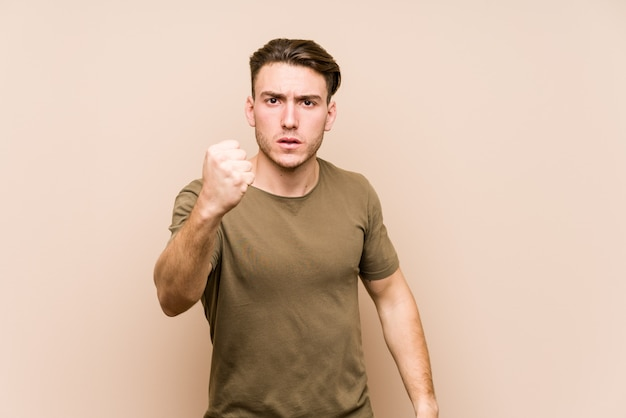 Young caucasian man posing isolated showing fist to camera, aggressive facial expression.