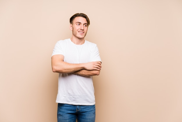 若い白人男性が組んだ腕に自信を持って孤立した笑顔をポーズします。