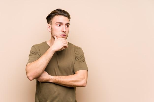 Молодой кавказский человек позирует изолировал вдумчивый глядя на копией пространства конус рот рукой.