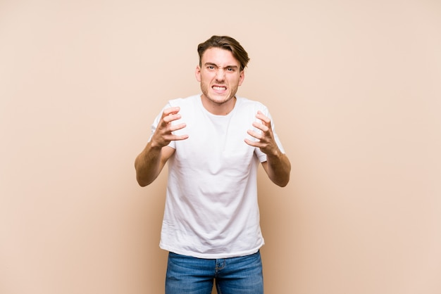 Young caucasian man posing isolated upset screaming with tense hands.