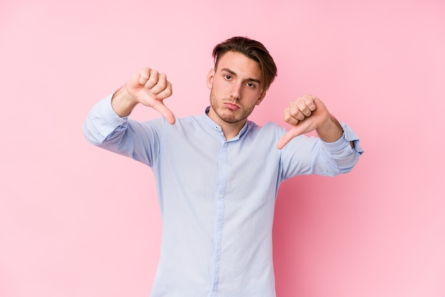 Young caucasian man posing in a pink  isolated showing thumb down and expressing dislike.