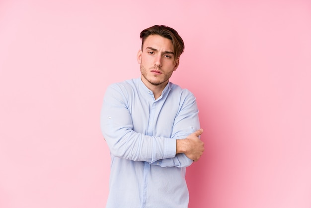 Young caucasian man posing in a pink wall isolated frowning face in displeasure, keeps arms folded.