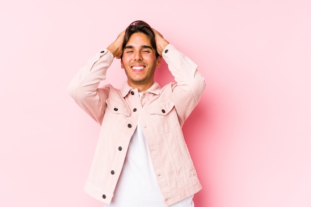 Young caucasian man posing in a pink wall isolated laughs joyfully keeping hands on head. happiness concept.