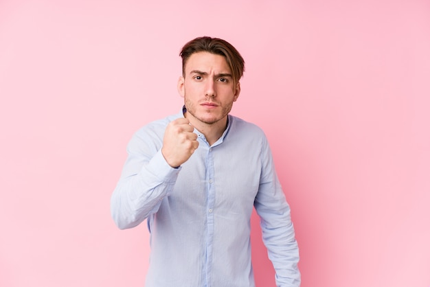 Young caucasian man posing in a pink wall isolated showing fist to camera, aggressive facial expression.