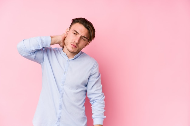 Young caucasian man posing in a pink wall isolated touching back of head, thinking and making a choice.