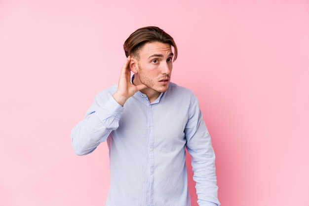 Young caucasian man posing in a pink wall isolated trying to listening a gossip.