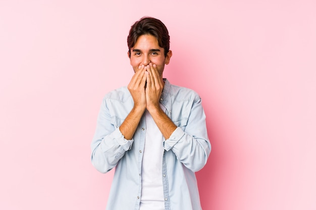 Young caucasian man posing in a pink wall laughing about something, covering mouth with hands.
