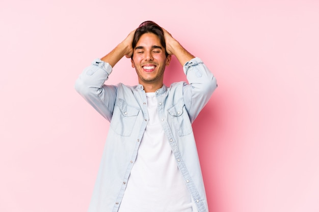 Young caucasian man posing in a pink wall laughs joyfully keeping hands on head.
